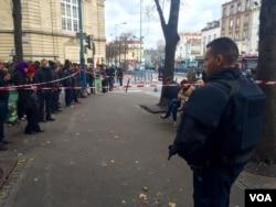 Crowd at standoff as riot policeman watches in Saint-Denis, Paris, Nov. 18, 2015. (D. Schearf/VOA)