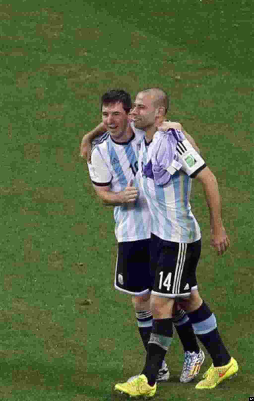 Argentina's Javier Mascherano and Lionel Messi celebrate after teammate Maxi Rodriguez scored the last penalty as Netherlands' players react at the end of the World Cup semifinal soccer match between the Netherlands and Argentina at the Itaquerao Stadium