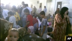 This image made from amateur video from Hama Revolution 2011purports to show families gathered around bodies of victims killed in Tremseh, Syria, July 13, 2012.