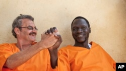 FILE - James Gatdet Dak, right, clasps hands with William Endley, left, a South African former defense colonel who also worked with the opposition, as they prepare to be released from prison after their death sentence was pardoned, in Juba, South Sudan, Friday, Nov. 2, 2018.