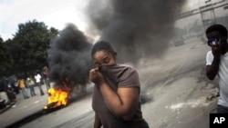 海地抗议者焚烧轮胎,大火熊熊,让一名妇女不得不掩面