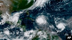 A satellite image from earlier this year shows several major storms and hurricanes in the Atlantic Ocean. Scientists say hgher temperatures could make such ocean storms worse.