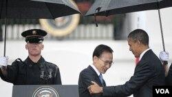 Presiden AS Barack Obama (kanan) menyambut kedatangan Presiden Korea Selatan, Lee Myung-bak di Gedung Putih di tengah hujan lebat (13/10).