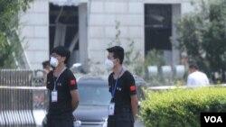 天津核心爆炸区周围居民楼间巡视的安检人员(美国之音记者东方)