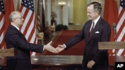 FILE - U.S. President George H.W. Bush (R) and Soviet President Mikhail Gorbachev shake hands following the signing of accords at the White House in Washington, June 1, 1990. Among deals reached was an agreement to reduce their countries' chemical weapons.