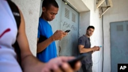 FILE - Students gather behind a business looking for a Internet signal for their smart phones in Havana, Cuba, April 1, 2014.