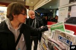 在法国西部的雷恩市,一名男士在报刊亭拿起一份《查理周刊》。(2015年1月14日)