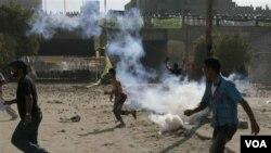 Para demonstran di Mesir melemparkan batu ke arah polisi, yang kemudian dibalas dengan gas air mata.