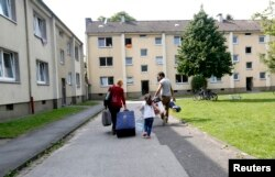 FILE - Lilas, a 4-year-old-refugee from Syria, and her parents walk to their refugee home in Muelheim an der Ruhr, Germany, after receiving articles for daily use prepared by donors at a distribution center on Aug, 20, 2015.