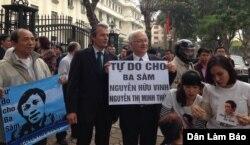 Ông Felix Schwarz, phụ trách Chính trị và Nhân quyền của Đại sứ quán Đức và dân biểu Đức Martin Patzelt cầm biểu ngữ kêu gọi trả tự do cho blogger Anh Ba Sàm và bà Nguyễn Thị Minh Thúy bên ngoài tòa án.