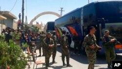 شام کے حکام کی جانب سے جاری کردہ اس تصویر میں باغیوں کو القلمون سے لے جانے کے لیے بسیں تیار کھڑی ہیں۔ 21 اپریل 2018
