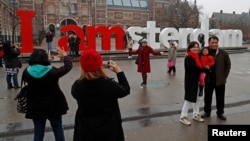 FILE - Tourists pose for photos outside the Rijksmuseum in central Amsterdam, Netherlands, Dec. 1, 2017.