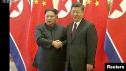 Poignée de main ferme entre le leader nord-coréen Kim Jong Un et le président chinois Xi Jinping, Beijing, le 28 mars 2018 (CCTV)