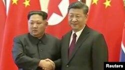 Shugaban Koriya ta Arewa Kim Jong Un shhands ya sha hannu da shugaban China Xi Jinping yayin ziyararsa