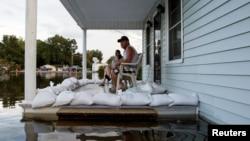 Megan Schexnayder dan David McNeely duduk di teras rumah mereka di Sorrento, Lousiana yang dikepung banjir (17/8). (Reuters/Edmund D. Fountain)