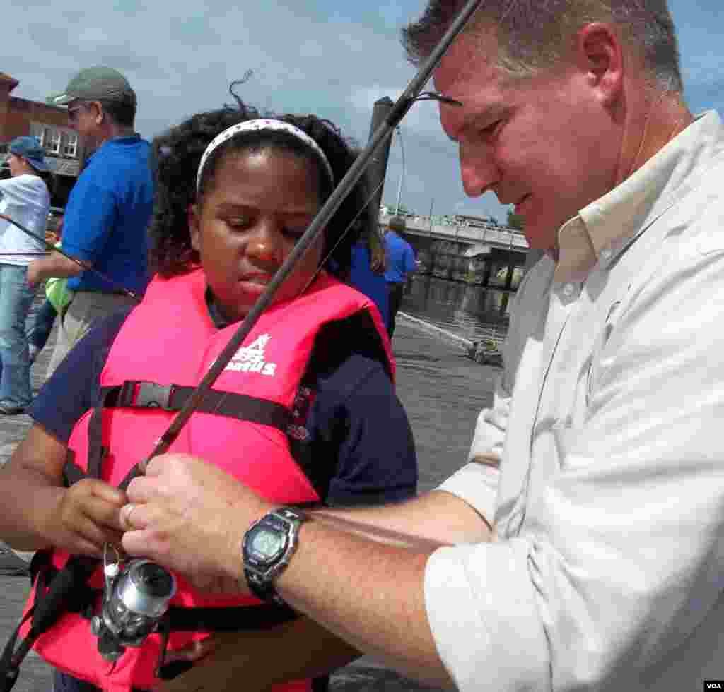 U.S. Fish and Wildlife Service volunteer Eric Lawton gives Makayla Gray her first fishing lesson on the Anacostia. (Rosanne Skirble/VOA)