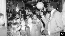 Harlem Globetrotter Meadowlark Lemon balances a basketball on his finger for children attending a children's benefit toy auction at New York's Tavern on the Green, April 23, 1979.