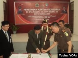 Kepala Kejaksaan Tinggi Jateng (tiga dari kiri, berkalung bunga) dan Walikota Solo (berkumis, paling kanan) menyaksikan penandatanganan MOU kantin kejujuran di sekolah. (Foto: VOA/Yudha)
