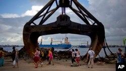 FILE - Tourists walk past an excavator shovel at the harbor of Havana, Cuba,Aug. 20, 2013.