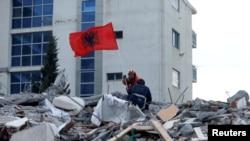 Seorang anggota SAR memasang bendera Albania selama pencarian korban di sebuah gedung yang runtuh di Durres, setelah gempa bumi mengguncang Albania, 28 November 2019. (Foto: Reuters/Florion Goga)
