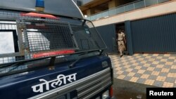 Policemen come out of one of the closed call centers in Mira-Bhayander, on the outskirts of Mumbai, India, Oct. 6, 2016.