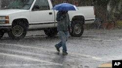 A man carries an umbrella as he walks across a street in San Francisco, Nov. 9, 2015.