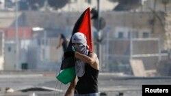 Un joven palestino sostiene una bandera durante enfrentamientos entre manifestantes palestinos y la policía israelí.