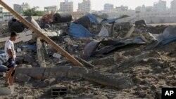 Cư dân Palestine kiểm tra thiệt hại sau vụ không kích của Israel tại thành phố Gaza, ngày 3/7/2014.