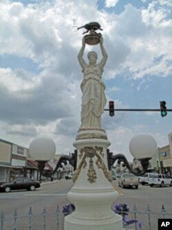 A statue on Main Street in Enterprise, Alabama, features a woman holding a large, black boll weevil above her head.