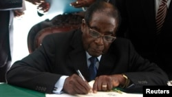 Zimbabwe President Robert Mugabe signs the country's new constitution into law in the capital Harare, replacing a 33-year-old document forged in the dying days of British colonial rule and paving the way for elections later this year, May 22, 2013.