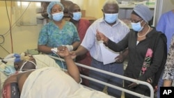 UN Deputy Secretary-General Asha-Rose Migiro, right, gives a thumbs up symbol to an employee of the WHO injured in Friday's suicide attack on UN headquarters, as she visits victims of the blast in Abuja, Nigeria, August 28, 2011