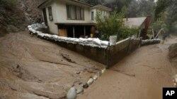 Une coulée de boue longe une maison protégée par des sacs de sable à Monrovia, en Californie, 6 janvier 2016.