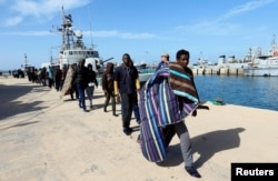 Migrants arrive at a naval base after they were rescued by the Libyan coast guard in Tripoli, Libya, March 13, 2018.