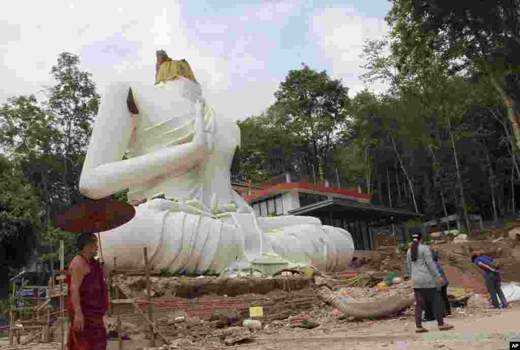 A Buddhist monk and villagers examine a damaged Buddha statue following an earthquake in Chiang Rai province, northern Thailand.