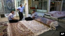 FILE - Iranian merchants wait for customers at a carpet market in Tehran's old main bazaar, in Iran, Aug. 10, 2015. Anger and frustration over the economy has been the main fuel for the surprise eruption of protests that began Dec. 28, 2017.