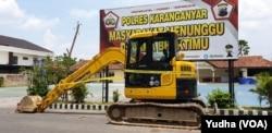 Barang bukti ekskavator dari tersangka penebangan pepohonan di hutan Lereng Gunjng Lawu Karangnyar masih dipasangi garis polisi di Mapolres Karanganyar, Selasa, 21 Januari 2020. (Foto: VOA/Yudha)