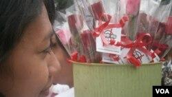 Relawan Demokrasi membawa bunga mawar untuk dibagikan kepada pengguna kendaraan bermotor. (VOA/Muliarta)