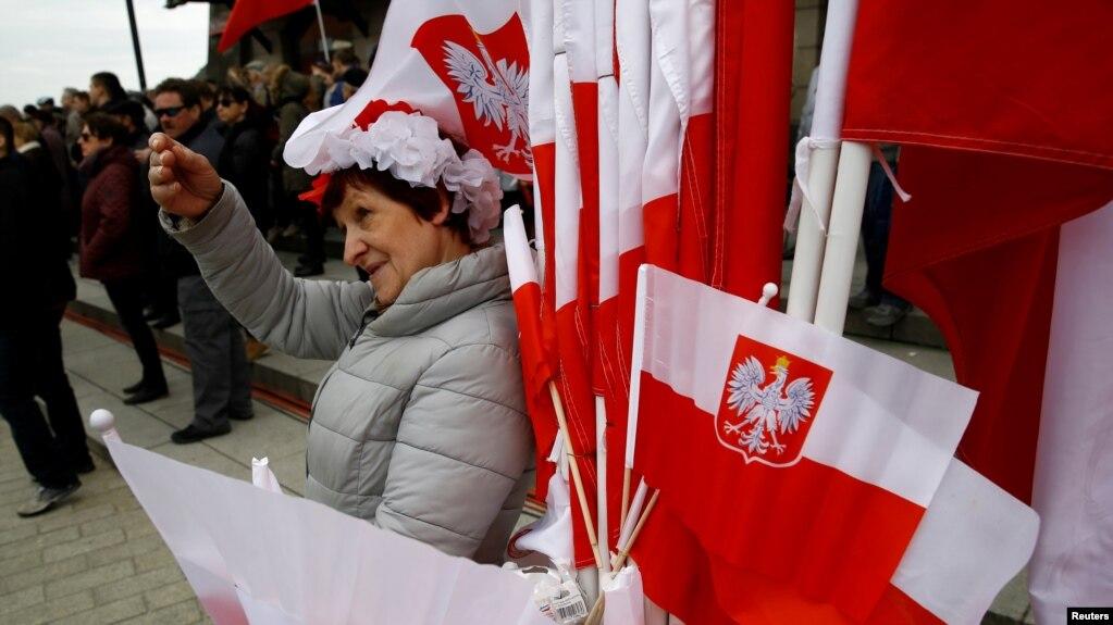 华沙街头一名小贩出售带有国徽的波兰国旗庆祝该国的宪法日。(2017年5月3日)(photo:VOA)