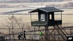 ພວກທະຫານເກົາຫຼີໃຕ້ກໍລັງກວດເບິ່ງຮົ້ວໜາມໝາກຈັບໃກ້ບ້ານປັນມູນຈອມ ເຂດປອດທະຫານທີ່ແບ່ງແຍກ ລະຫວ່າງສອງເກົາຫຼີ ຫຼື DMZ.