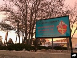 The sun sets on a sign in front of the Archdiocese of Santa Fe offices in Albuquerque, N.M., Nov. 29, 2018. Archbishop John Wester announced Thursday that the archdiocese will be filing for Chapter 11 bankruptcy protection, as the Catholic church in New Mexico has settled numerous claims of sexual abuse by clergy over the years and is close to depleting its reserves.
