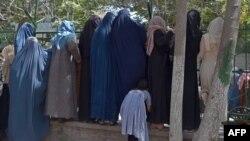 Las mujeres afganas desplazadas internamente, que huyeron de la provincia del norte debido a la batalla entre talibanes y fuerzas de seguridad afganas, se reúnen para recibir alimentos gratuitos ded manos de hombres chiítas en Kabul el 13 de agosto de 2021.