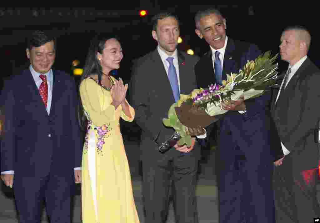 Tổng thống Obama nhận hoa từ một nữ sinh Việt Nam khi bước xuống máy bay tại sân bay Nội Bài ở Hà Nội, tối ngày 22/5/2016