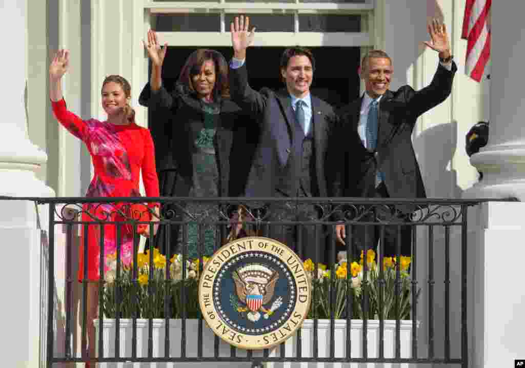President Barack Obama and first lady Michelle Obama wave with Canadian Prime Minister Justin Trudeau, and his wife Sophie Gregoire, on the Truman Balcony during the arrival ceremony on the South Lawn of the White House in Washington.