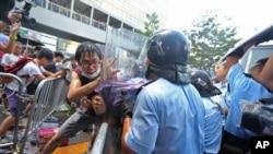 Polisi anti huru hara berupaya menghalau para demostran yang memaksa untuk menuju kantor pemerintah pusat dan berunjuk rasa di Hong Kong, Sabtu pagi (27/9).