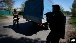 Pro-Russian armed militants prepare to inspect a truck near Slovyansk, eastern Ukraine, April 25, 2014.