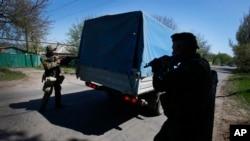 Kelompok bersenjata pro Rusia memeriksa sebuah truk dekat Slovyansk, Ukraina bagian timur, 25 April 2014.