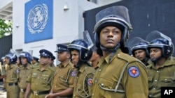 Police officers stand guard in front of the UN head office during a protest in Colombo, Sri Lanka, March 2, 2012. The UN Human Rights Council is currently debating a proposed resolution to probe alleged war crimes in the final months of the Sri Lankan civ