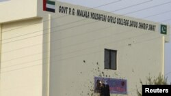 سوات کے شہر سیدو شریف کے گرلز کالج کی ایک طالبہ کالج کی عمارت پر آویزاں ملالہ یوسف زئی کی تصویر پھاڑ رہی ہے