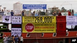 Cambodian non-governmental organization (NGOs) activists shout slogans during a protest against a proposed Don Sahong dam, in a tourist boat along the Tonle Sap river, in Phnom Penh, Cambodia, Sept. 11, 2014.