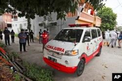 Sukarelawan bergabung dengan kerabat untuk berdoa di dekat ambulans yang membawa jenazah korban COVID-19, sebelum mengantarnya ke pemakaman untuk dimakamkan, di Bekasi di pinggiran Jakarta, 11 Juli 2021. (AP)